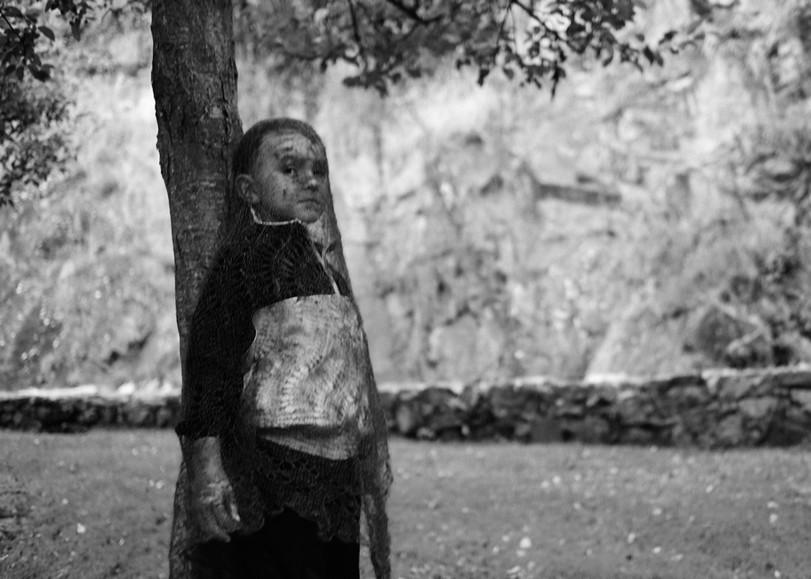 Photo en noir et blanc d'un enfant recouverte d'un voile transparents devant un arbre. Image pour Andromaque, une pièce de théâtre de Léna Paugam au Moulin du Roc à Niort