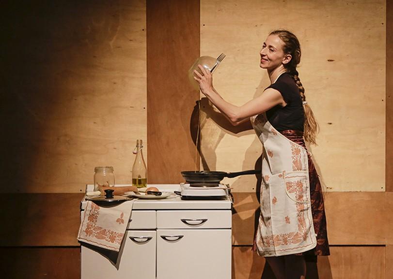 Une femme en tablier versant le contenant d'un bol dans une poêle pour Bellissima soli feminista, spectacle de danse de AMBRA SENATORE et CLAUDIA CATARZI au Moulin du Roc à Niort