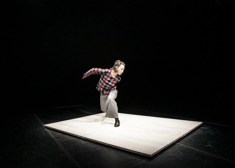 Une femme dansant sur un carré de bois blanc au centre d'une pièce obscure. Image de Bellissima soli feminista, spectacle de danse de AMBRA SENATORE et CLAUDIA CATARZI au Moulin du Roc à Niort