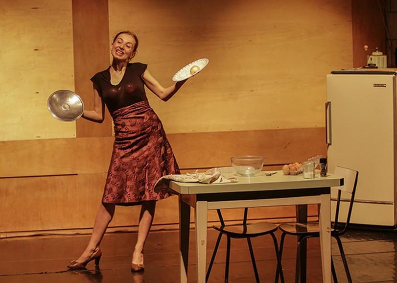 Une femme tenant dans une main une assiette et dans l'autre un couvercle dans une cuisine. Image de Bellissima soli feminista, spectacle de danse de AMBRA SENATORE et CLAUDIA CATARZI au Moulin du Roc à Niort