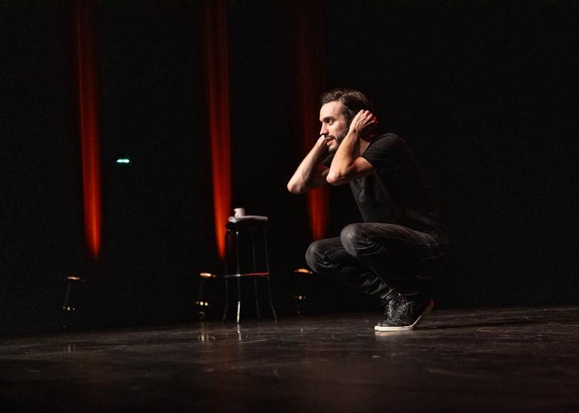 Image de Laurent Sciamma accroupi, seul sur scène pour Bonhomme, spectacle stand-up utour du genre et des nouvelles masculinités au Moulin du Roc à Niort