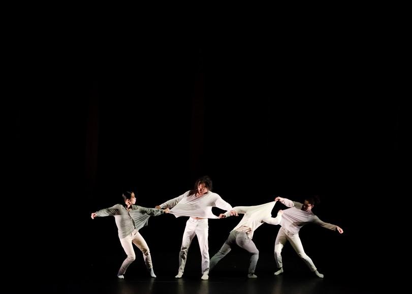 Image du spectacle Butterfly, spectacle de danse hip-hop de MICKAËL LE MER / CIE S'POART au Moulin du Roc à Niort. Quatre danseurs vêtus de blanc s'éloignent les uns des autres en tirant sur les vêtements de leur voisin.