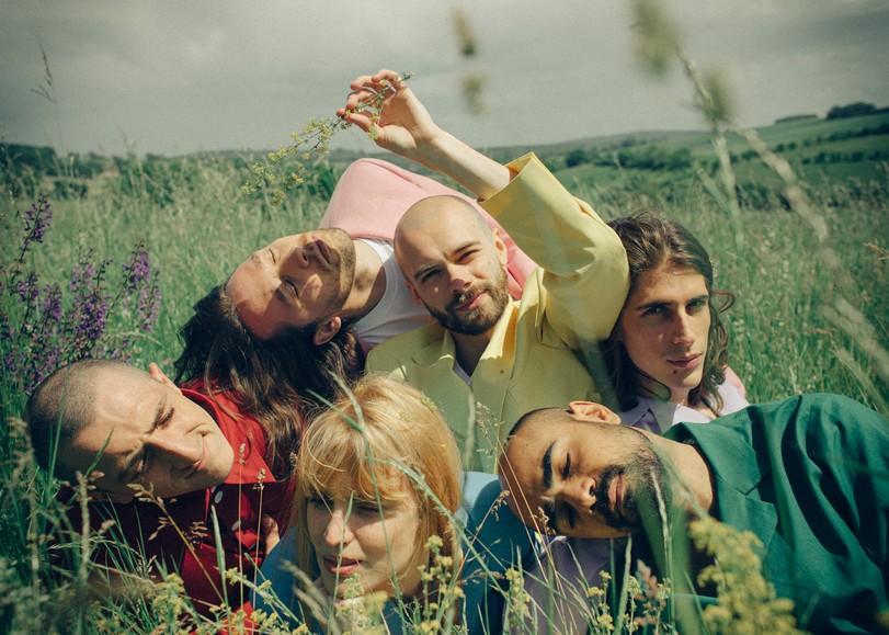 Portrait des six membres du groupe Catastrophe allongés dans un chant, vêtus de costumes aux couleurs vives. Image pour la nouvelle comédie musicale de Catastrophe au Moulin du Roc à Niort