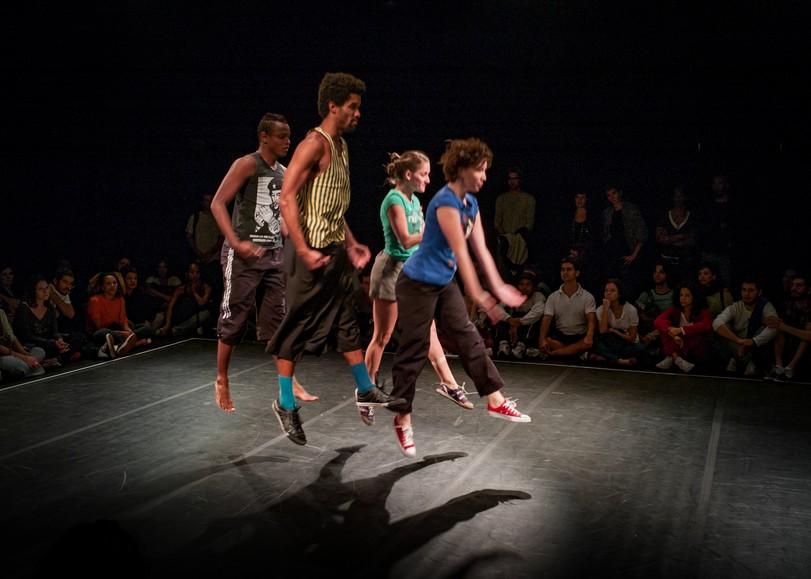 Quatre danseurs aux tenues colorées sautant au centre du plateau. Image de Ce dont nous sommes faits, spectacle de danse de Lia Rodrigues au Moulin du Roc à Niort
