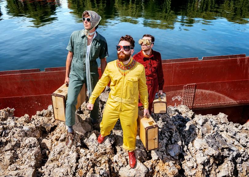 Portrait du trio de Théo Ceccaldi, en tenus colorées, devant un lac et tenant chaun une valise à la main. Image de Django de Théo Ceccaldi, un concert jazz au Moulin du Roc à Niort