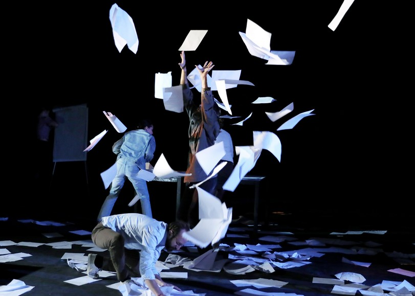 Trois personnes dans un bureau jetant des feuilles en l'air. Image pour En réalité, une pièce de théâtre d'Alice Vannier d'après Pierre Bourdieu au Moulin du Roc à Niort