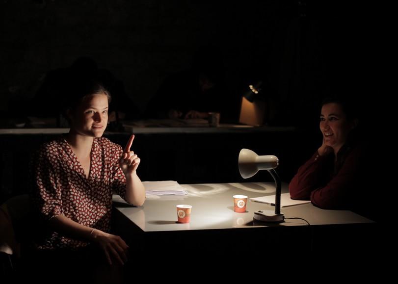 Deux femmes assises à un bureau. Image pour En réalité, une pièce de théâtre d'Alice Vannier d'après Pierre Bourdieu au Moulin du Roc à Niort