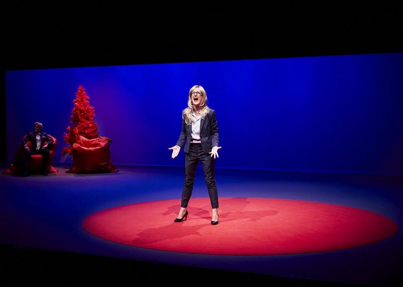 Une femme habillée en costard crie, les mains dirigées vers le public. Image de Entreprise, pièce de théâtre dAnne-Laure Liégois sur le monde du travail, au Moulin du Roc à Niort