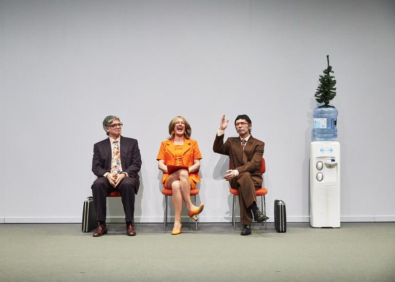 Trois comédiens assis sur des chaises oranges sont dans une salle d'attente, à côté d'une fontaine à eau sur laquelle se trouve un sapin en plastique. Image de Entreprise, pièce de théâtre dAnne-Laure Liégois sur le monde du travail, au Moulin du Roc à Niort