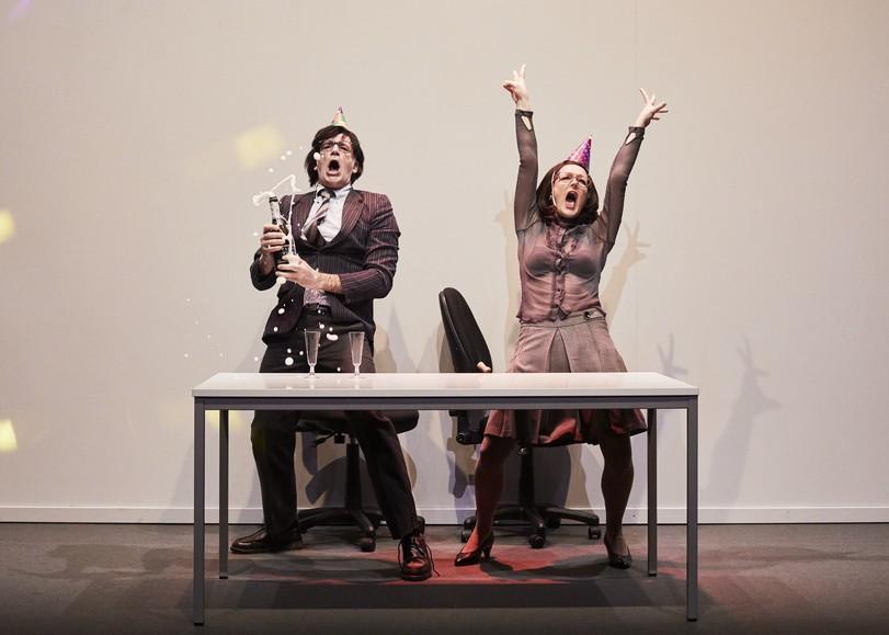 Un homme et une femme debout derrière un bureau, criant de joie. L'homme ouvre une bouteille de champagne et la femme tend les bras vers le ciel. Image de Entreprise, pièce de théâtre dAnne-Laure Liégois sur le monde du travail, au Moulin du Roc à Niort
