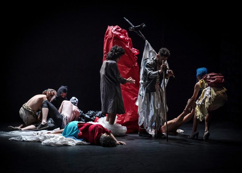 Danseurs par terre ou debout, vêtus de vêtements colorés, l'un d'entre eux porte une croix sur son dos. Image de FURIA, spectacle de danse de Lia Rodrigues au Moulin du Roc à Niort