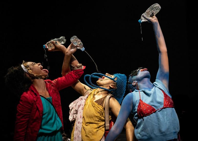 Trois danseurs aux tenues colorées buvant de l'eau depuis une bouteille en plastique tendue au-dessus de leurs têtes. Image de FURIA, spectacle de danse de Lia Rodrigues au Moulin du Roc à Niort