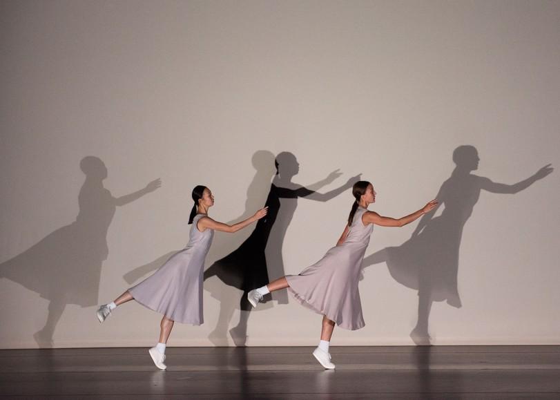 Deux danseuses dans la même position, leurs ombres se reflétant sur le mur. Image pour Fase , spectacle de danse d'ANNE TERESA DE KEERSMAEKER au Moulin du Roc à Niort