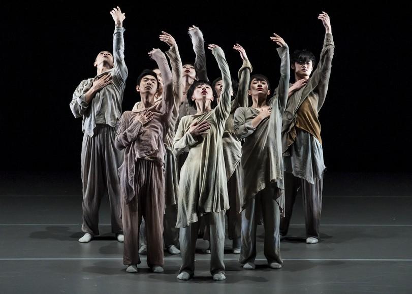 Un groupe de danseurs vêtus de vêtements sombres et ambles, une main sur la poitrine et l'autre tendue vers le ciel. Image de From In, spectacle de danse du XIEXIN DANCE THEATRE au Moulin du Roc à Niort