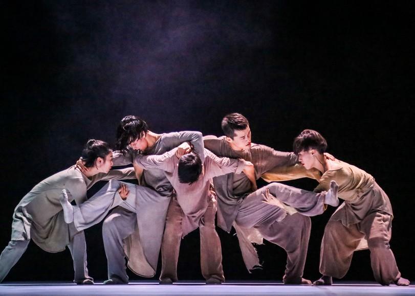 Un groupe de danseurs vêtus de vêtements ambles, se tenant par les épaules et les jambes. Image de From In, spectacle de danse du XIEXIN DANCE THEATRE au Moulin du Roc à Niort