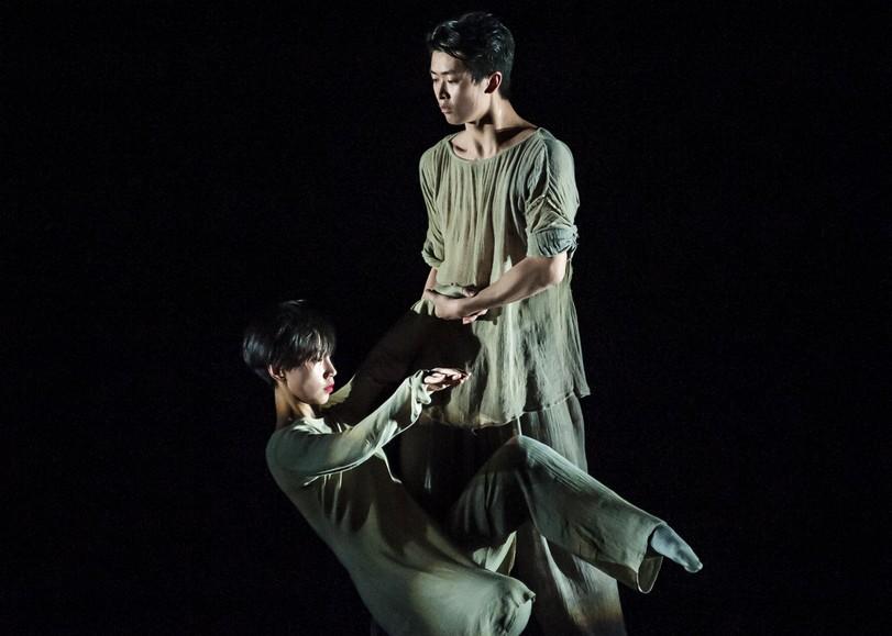 Deux danseurs vêtus de vêtements amples se tiennent par la main, l'un debout, l'autre se baissant vers le sol. Image de From In, spectacle de danse du XIEXIN DANCE THEATRE au Moulin du Roc à Niort