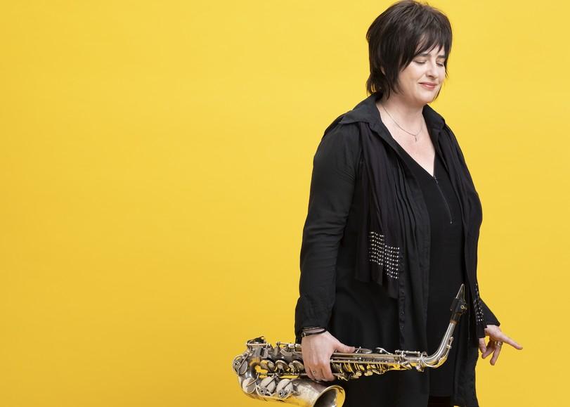"""Portrait de la saxophoniste Géraldine Laurent sur fond jaune. Enconcert au Moulin du Roc à Niort pour son album jazz """"Cooking"""""""