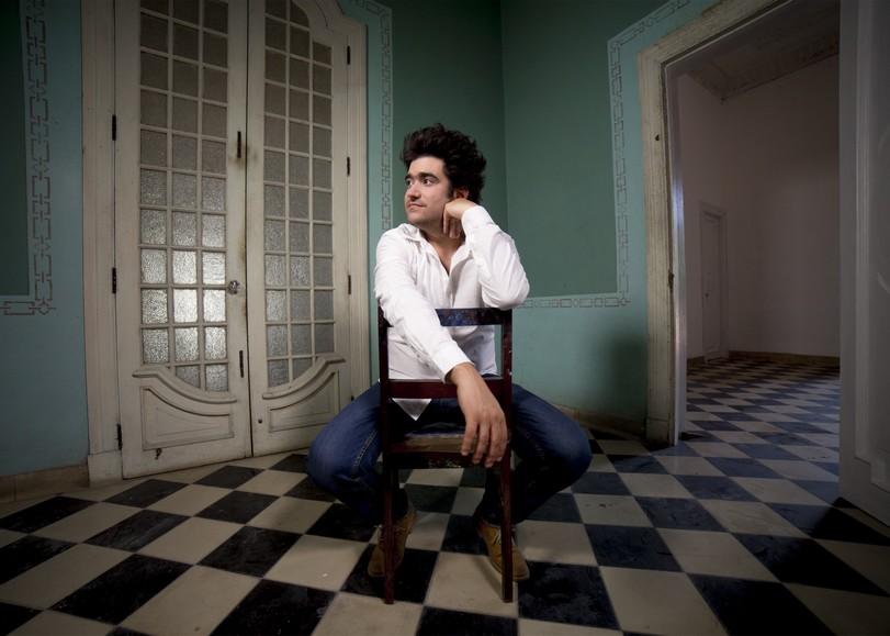 Portrait d'Harold Lopez Nussa assis sur une chaise dans une salle bleue au sol à carreaux noirs et blancs. Harold Lopez Nussa sera en concert au Moulin du Roc à Niort