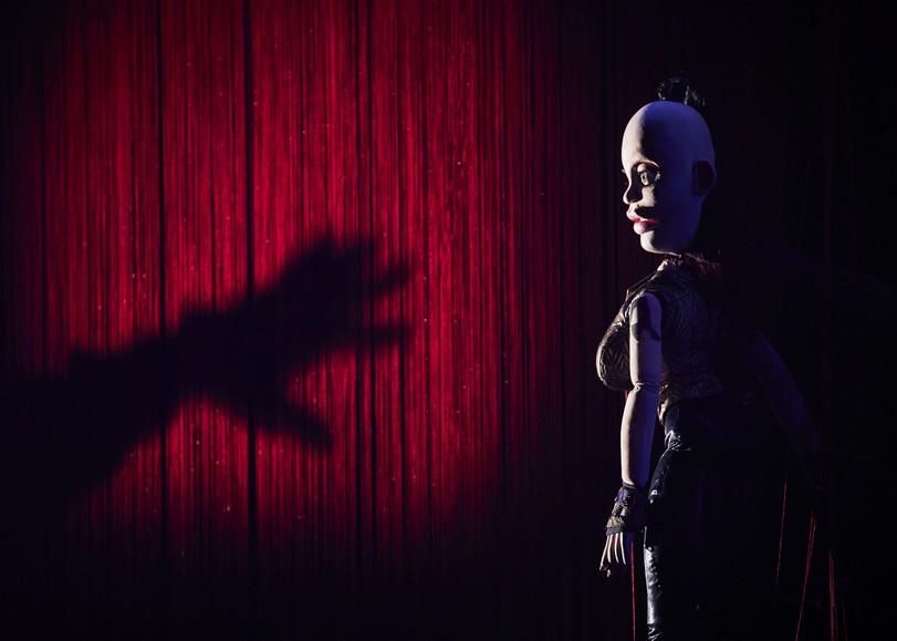 Marionnette de femme se tenant devant un rideau rouge, l'ombre d'une main s'approchant d'elle. Image pour Hen, spectacle marionnette et cabaret trans de Johanny Bert au Moulin du Roc à Niort