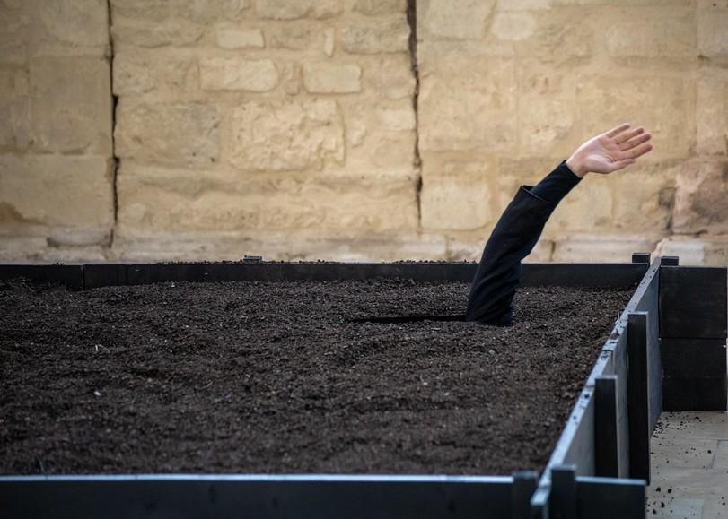 Un bras dépassant d'un bac rempli de terre dans le spectacle Histoire de fouilles, pièce de théâtre autour des déchets et de l'environnement de David Whal au Moulin du Roc à Niort