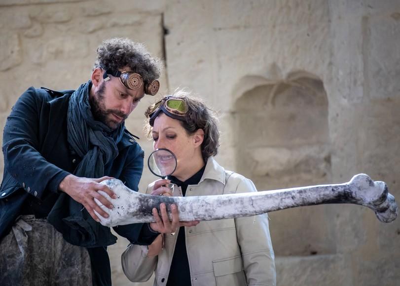 Un homme et une femme examinant un os géant à la loupe dans le spectacle Histoire de fouilles, pièce de théâtre autour des déchets et de l'environnement de David Whal au Moulin du Roc à Niort
