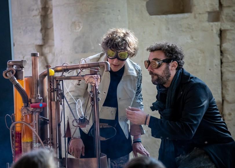 Un homme et une femme manipulant une machine en cuivre à multiples tuyaux pour le spectacle Histoire de fouilles, pièce de théâtre autour des déchets et de l'environnement de David Whal au Moulin du Roc à Niort