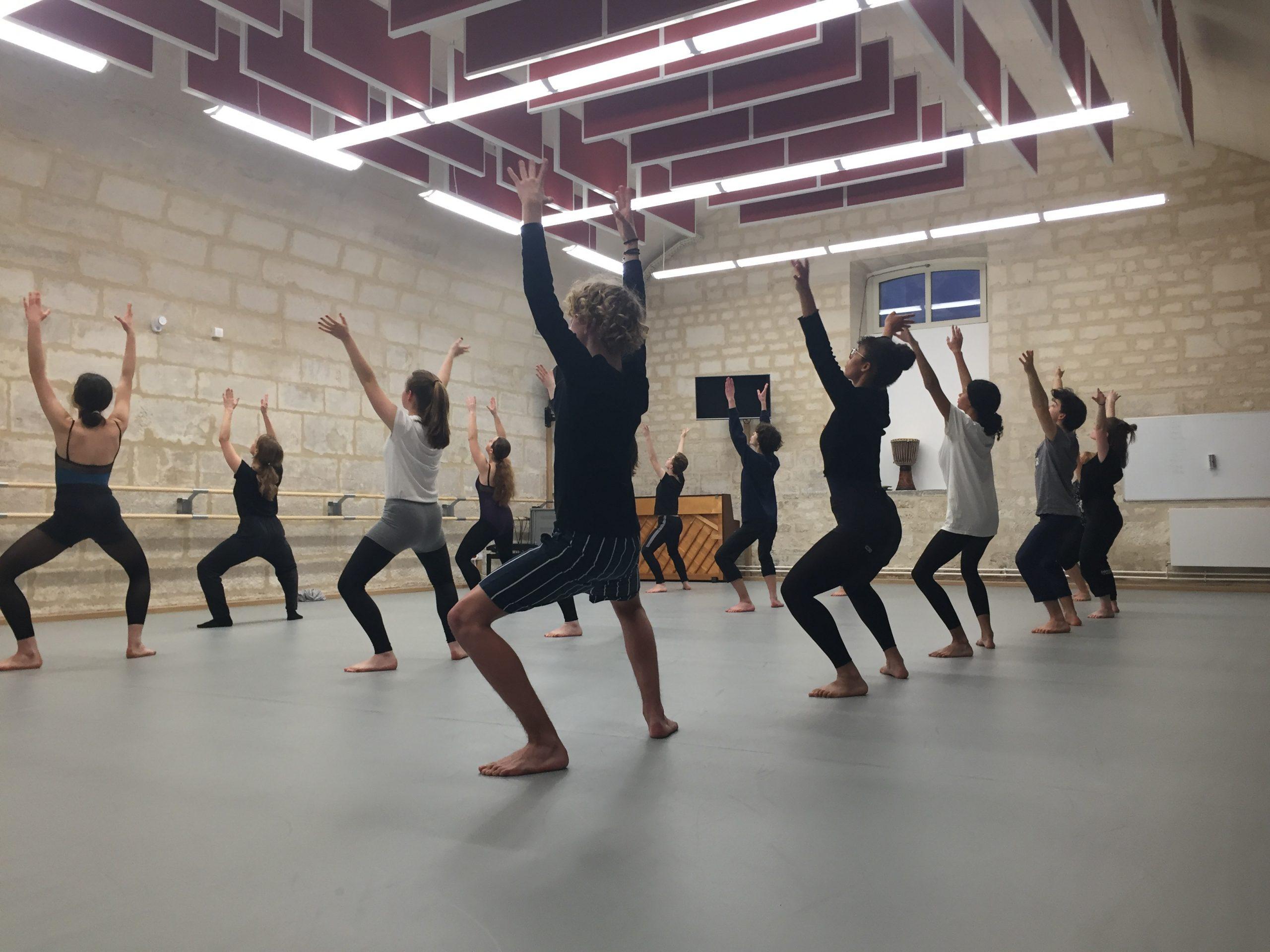 Groupe de danseurs levant les bras au ciel dans le cadre d'une masterclass et un ateliers proposés par le Moulin du Roc à, Scène nationale à Niort