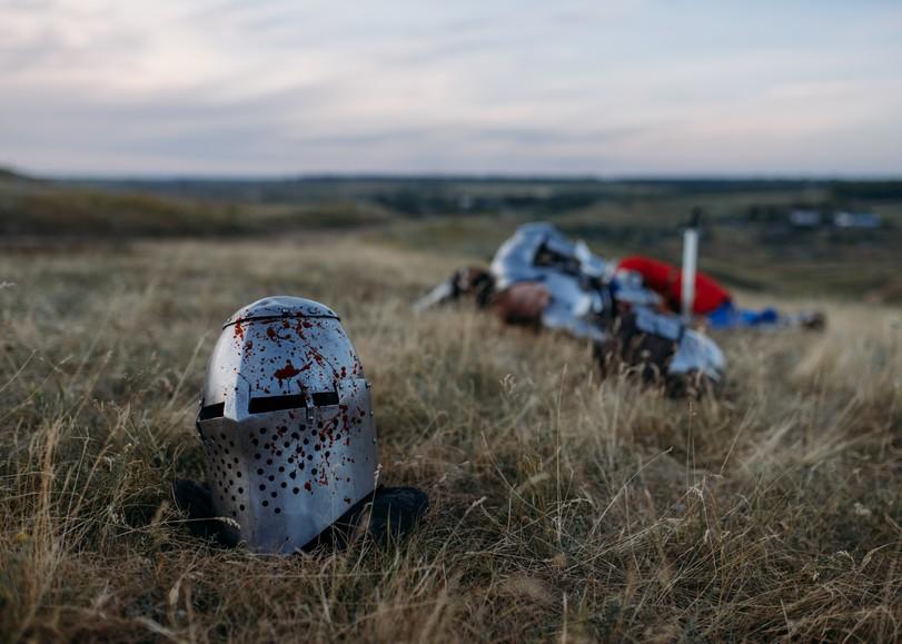 Image d'un champ dans lequel on aperçoit au premier plan un casque ensanglanté et derrière lui, un soldat à terre. Une image illustrant la pièce de théâtre Ici le temps se déroule de MASH-UP PRODUCTION d'après Le Roi Lear, au Moulin du Roc à Niort