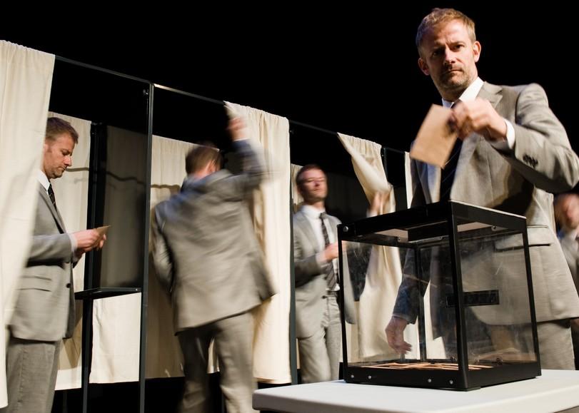 Un bureau de vote, au premier plan un homme mettant son enveloppe dans l'urne. Image pour Influences de THIERRY COLLET, spectacle de magie mentale au Moulin du Roc à Niort