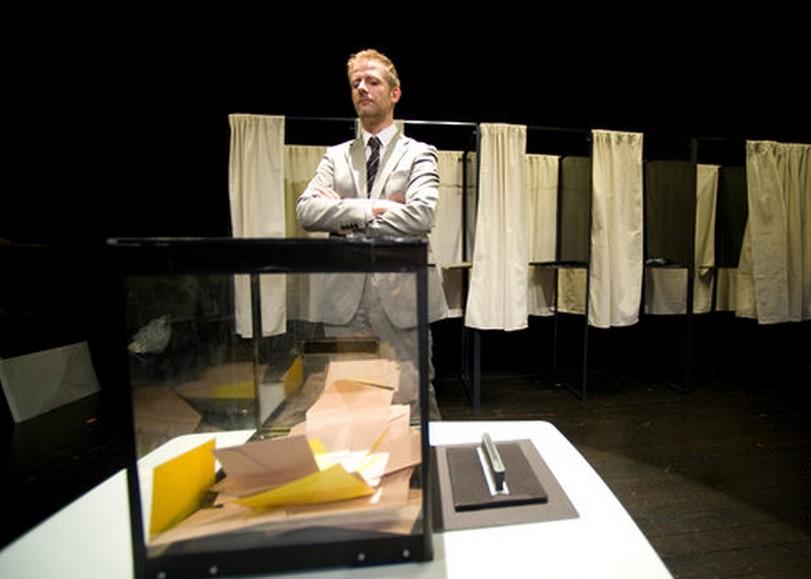 Un bureau de vote, un homme regardant une urne remplie d'enveloppes. Image pour Influences de THIERRY COLLET, spectacle de magie mentale au Moulin du Roc à Niort