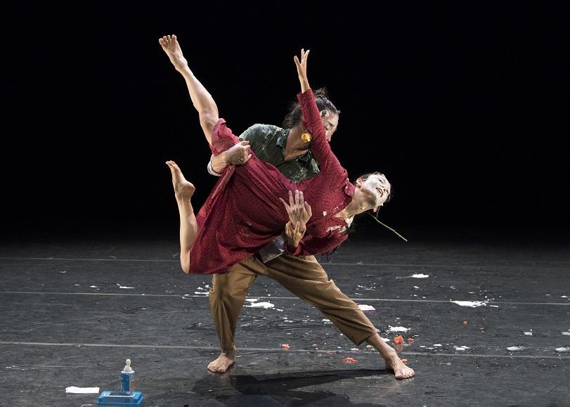 Un coupe de danseurs, l'homme portant la femme, une fleur dans la bouche. Image de Is it worth to save us, spectacle de danse de KAORI ITO et MIRAÏ MORIYAMA au Moulin du Roc à Niort