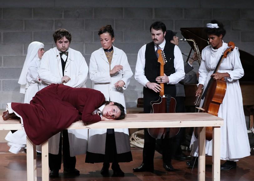 Un femme allongé sur une table, des médecin-musiciens l'entourent. Image pour La Chute de la maison de SAMUEL ACHACHE et JEANNE CANDEL, une pièce de théâtre musical au Moulin du Roc à Niort