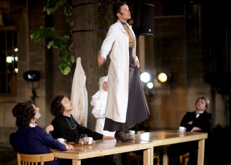 Une femme vêtue d'une blouse blanche, debout sur une table. Image pour La Chute de la maison de SAMUEL ACHACHE et JEANNE CANDEL, une pièce de théâtre musical au Moulin du Roc à Niort