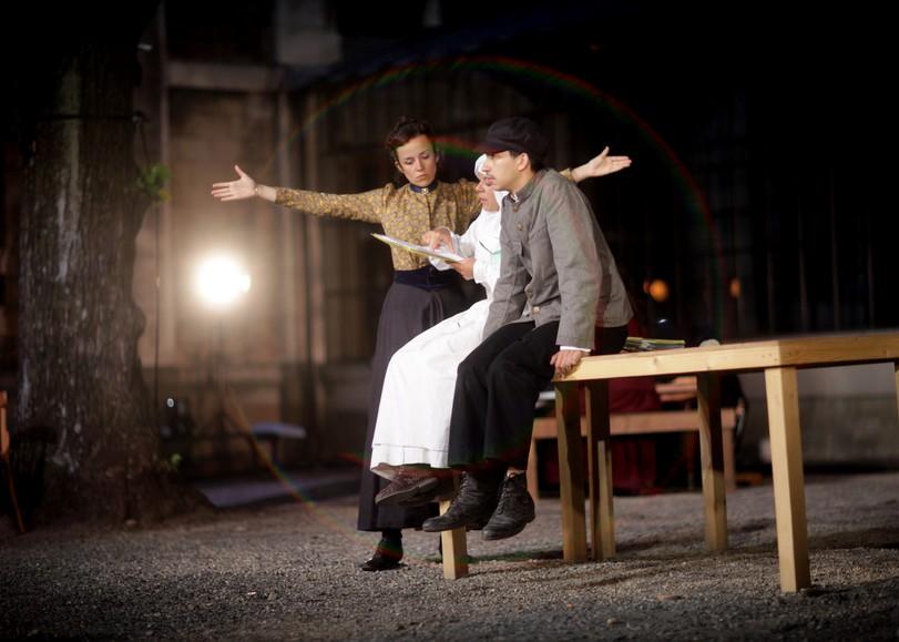 Deux comédiens assis sur une table et une femme debout les bras écartés. Image pour La Chute de la maison de SAMUEL ACHACHE et JEANNE CANDEL, une pièce de théâtre musical au Moulin du Roc à Niort
