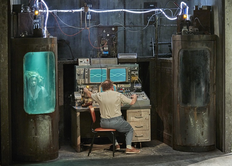 Un homme aux commandes d'une machine de téléportation. Une femme est enfermée dans le bac à sa gauche. Image de La Mouche, pièce de théâtre VALÉRIE LESORT & CHRISTIAN HECQ au Moulin du Roc à Niort