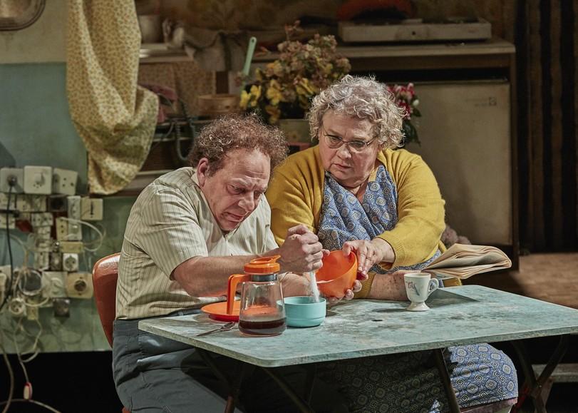 Un homme et une femme assis à une table de camping, versant du sucre dans un bol. Image de La Mouche, pièce de théâtre VALÉRIE LESORT & CHRISTIAN HECQ au Moulin du Roc à Niort