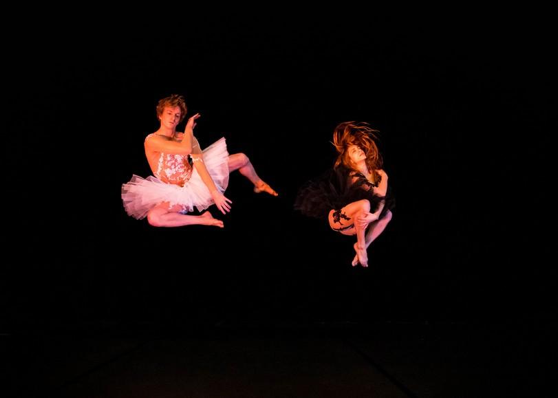 Deux danseurs en tutus blanc et noir sautant dans les airs. Image pour Le Lac des cygnes, spectacle de cirque de la compagnie L'éolienne au Moulin du Roc à Niort