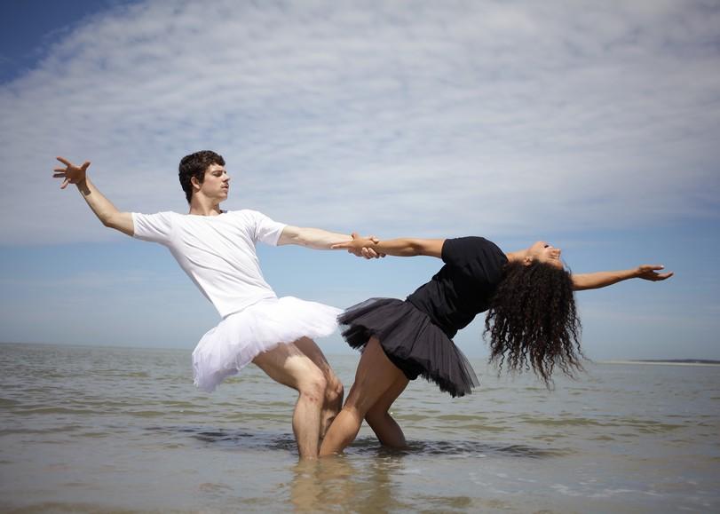 Deux danseurs en tutus, l'un blan, l'autre noir, se tenant par la main et se penchant en arrière, les pieds dans l'eau. Image pour Le Petit lac, spectacle de cirque de la compagnie L'éolienne à découvrir en famille au Moulin du Roc à Niort