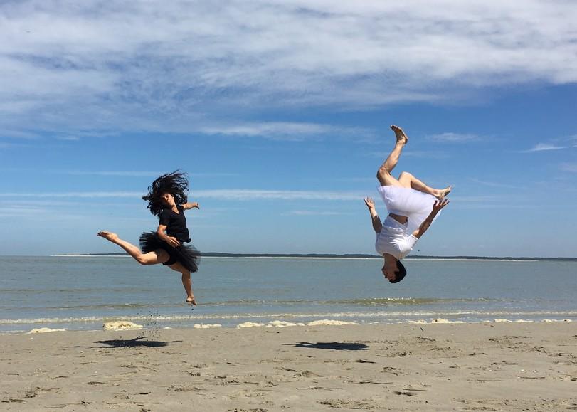 Deux danseurs en tutus, l'un blan, l'autre noir, sautant sur le sable (tête en bas ou tête en haut). Image pour Le Petit lac, spectacle de cirque de la compagnie L'éolienne à découvrir en famille au Moulin du Roc à Niort