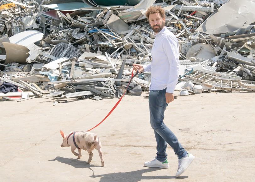 Un homme tenant un cochon en laisse devant un amas de câbles électriques dans le spectacle Le sale discours, pièce de théâtre autour des déchets et de l'environnement de David Whal au Moulin du Roc à Niort