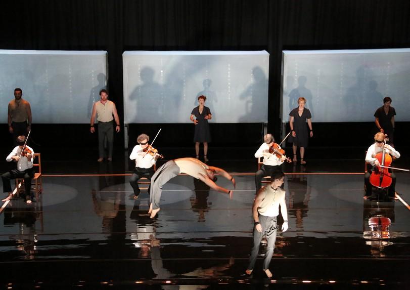 Un plateau au sol brillant, des musiciens les yeux bandés et des acrobates. Image pour Opus, spectacle de cirque de la compagnie Circa et du Quatuor Debussy au Moulin du Roc à Niort
