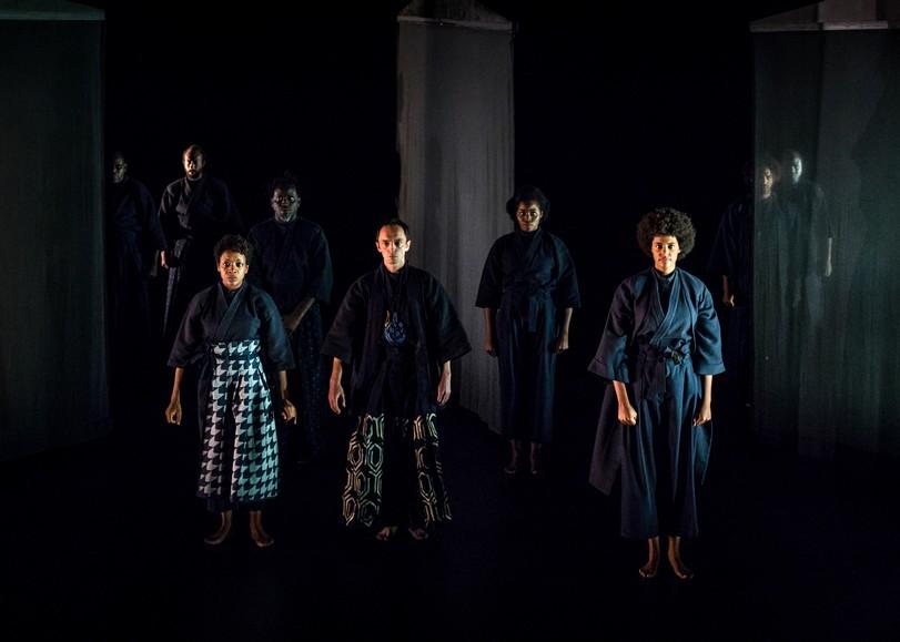 Sept comédiens debout dans la pénombre et vêtus de kimonos. Image pour Othello, une pièce de théâtre d'Arnaud Churin au Moulin du Roc à Niort