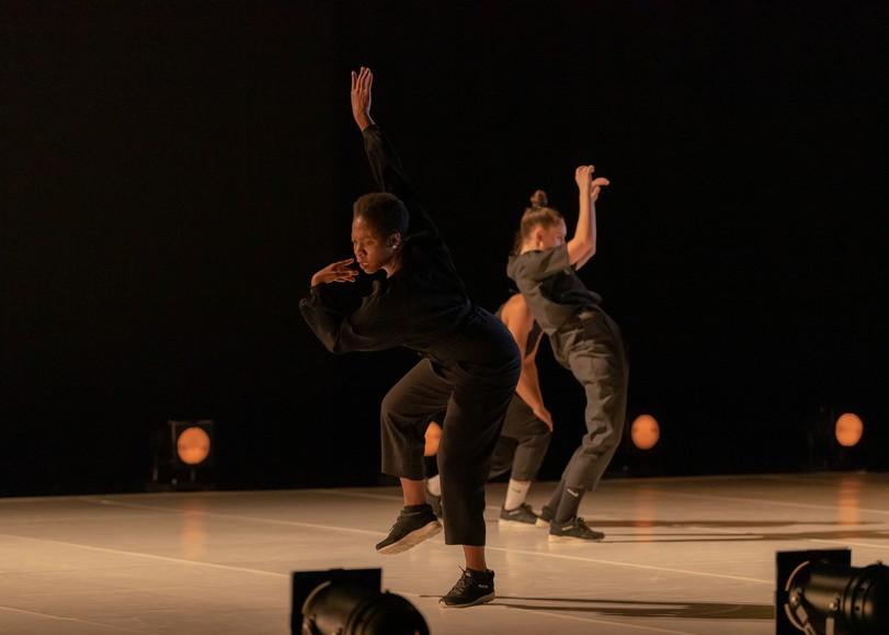 Danseuses vêtues de noir, photographiées en plein mouvement, lumière chaude. Image pour Queen Blood, spectacle de danse d'Ousmane Sy au Moulin du Roc à Niort