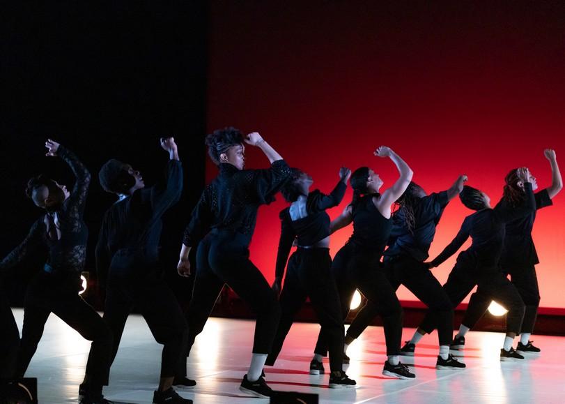 Groupe de danseuses alignées, prises de dos, le bras droit levé, sur fond rouge. Image pour Queen Blood, spectacle de danse d'Ousmane Sy au Moulin du Roc à Niort