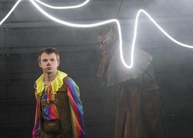 Un garçon au nez rouge et vêtements coloré, sous des néons de lumière blanche. Image pour Rémi, pièce de théâtre de JONATHAN CAPDEVIELLE au Moulin du Roc à Niort