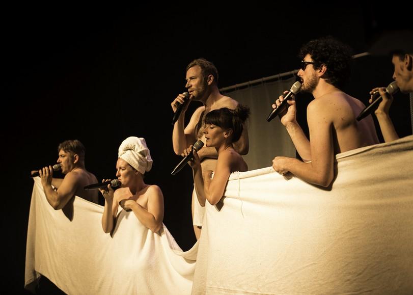 Les chanteurs a capela du spectacle Shower Power, dénudés, se cachant derrière une serviette de bain géante. Un spectacle programmé au Moulin du Roc à Niort