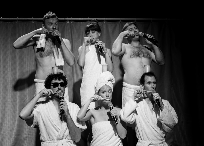 Les chanteurs a capela du spectacle Shower Power se brossant les dents vêtus d'une serviette de bain, le micro à la main. Un spectacle programmé au Moulin du Roc à Niort