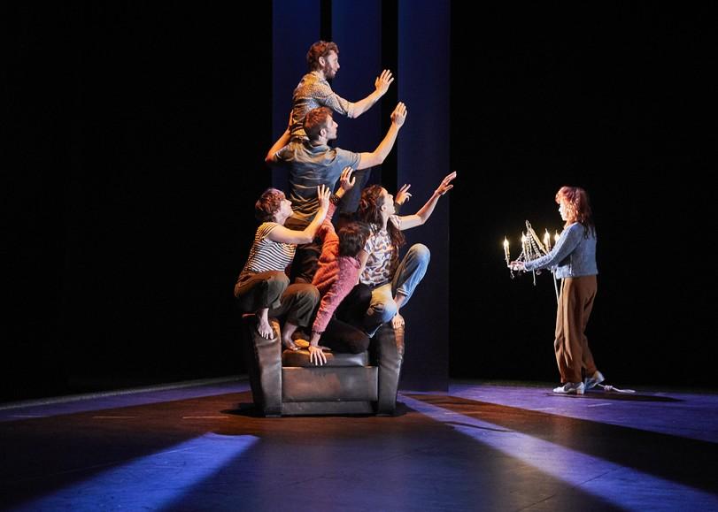 Les comédiens de Un furieux désir de bonheur, une pièce de théâtre de Catherine Verlaguet au Moulin du Roc à Niort, sur un fauteur, le regard et les mains dirigés vers une femme portant un chandelier.