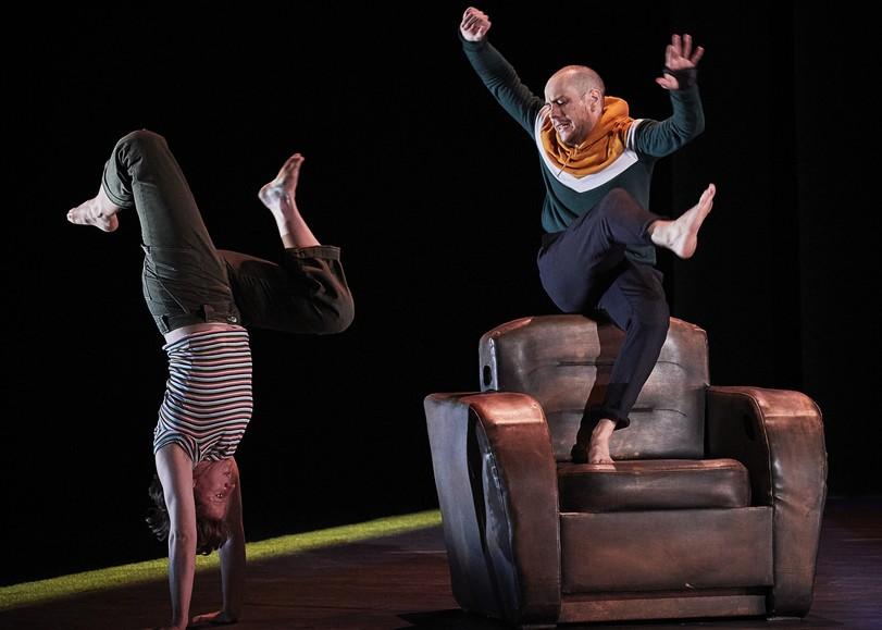 Un bomme faisant l'équilibre sur les mains et l'autre sautant sur un fauteuil en cuir. Image de Un furieux désir de bonheur, une pièce de théâtre de Catherine Verlaguet au Moulin du Roc à Niort