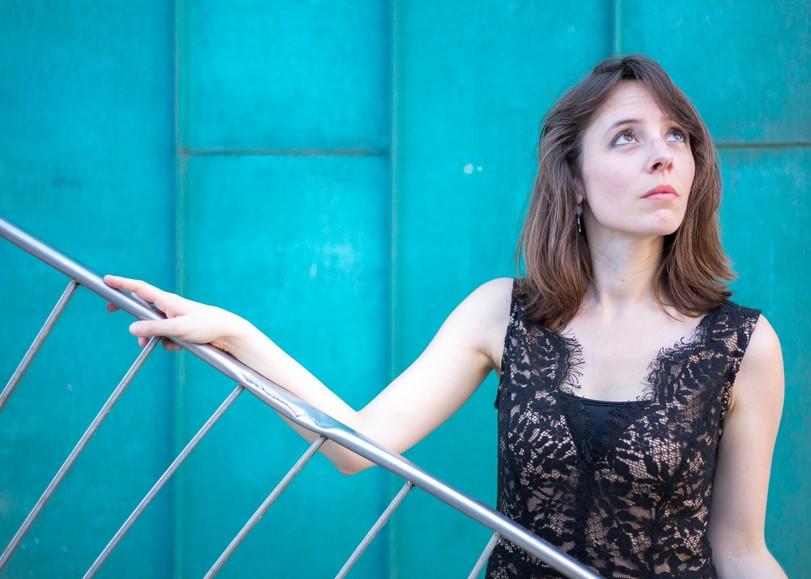 Portrait de Maude Gratton en robe noire devant un mur bleu. Image du Week-end Beethowen, concert de Maude Gratton et l'ensemble Il Convito au Moulin du Roc à Niort